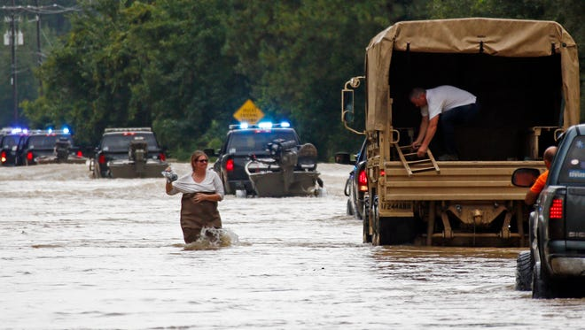 """Jeff Robinson lowers a ladder from a Louisiana National Guard truck as his wife wades through flood waters from the Natalbany River near their home in Baptist, La., Saturday. Robinson was seeking a boat ride from state wildlife agents to pick up his wife and children when the National Guard truck arrived. A slow-moving storm that has dumped almost a foot of rain in Louisiana parishes south and west and Mississippi counties north of the Mississippi-Louisiana state line, are in for more rain. National Guard soldiers and other officials in boats and helicopters plucked more than 1,000 people from their homes and cars as """"unprecedented, historic"""" flooding swamped Louisiana."""
