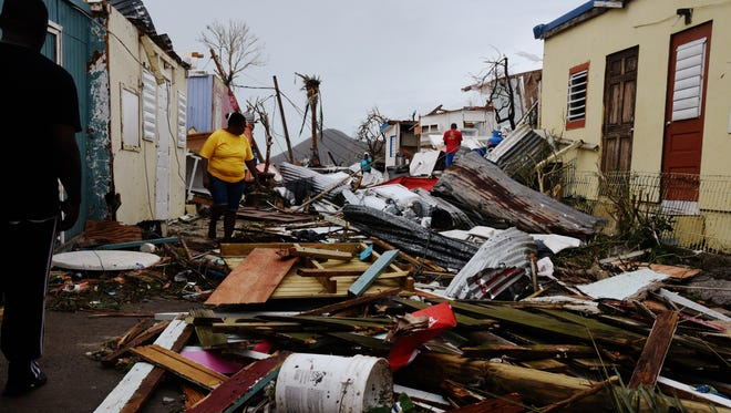 Hurricane Irma pummeled St. Maarten/St. Martin and other northern Caribbean islands Wednesday as it tore a disastrous path through the Atlantic toward the continental U.S. Here, a woman treads through the wreckage of Cay Bay, a largely low-income community, after the storm had passed. Local officials instituted a curfew to little effect.