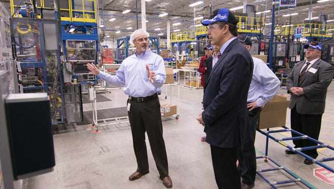 General manager of engineering Edward Ramirez, left, talks to U.S. Rep. Mike Bishop, in foreground, about the processes involved in manufacturing specialized hoses and tubing for the auto industry in a tour of TG Fluid Systems in Brighton Wednesday, Jan. 24, 2018.