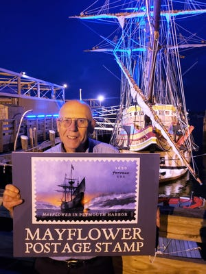 George McKay of the Plymouth Rock Stamp Club holds an image of the new Mayflower stamp in front of the illuminated ship on the Plymouth waterfront.