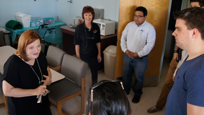 Patti West-Okiri, left, a social work professor from WNMU, takes a group of her colleagues from the university on a tour of the Disabilities Resource Center in Silver City on Tuesday.