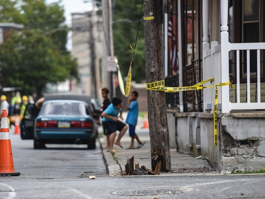 Kids play under the caution tape near a utility pole that was struck after an out of control Lebanon Transit bus, damaged in a previous crash, carrying 23 passengers came stop at Church and Gannon streets after the driver intentionally stuck a dumpster to stop the bus.