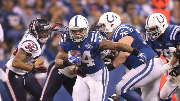 Indianapolis Colts Trent Richardson break through the Texans defensive line. The Indianapolis Colts defeated the Houston Texans 25-3 in their NFL football game Sunday, December 15, 2013, afternoon at Lucas Oil Stadium.