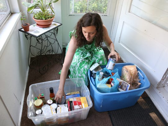 Amy Cavalier, administrator of a Buy Nothing group in a Beechwood, Homestead Heights, and Culver-Winton neighborhood, sorts through donated foods at her home before taking them to the Blessing Box at the Covenant United Methodist Church on Culver Road in Rochester Thursday, June 22, 2017.