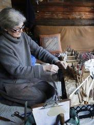 Victoria Jungwirth works on a miniature birchbark canoe