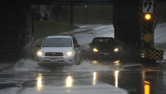 Vehicles splash their way through and underpass Tuesday evening in Mansfield.