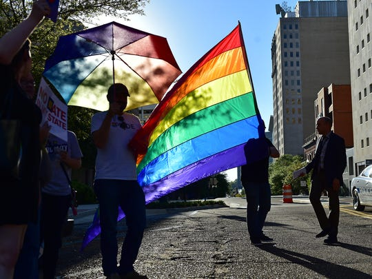Protesters hold a rainbow flag to show their opposition of HB 1523 Monday during a rally on Capitol Street in front of the Governor's Mansion.