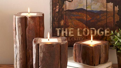 """This undated photo provided by Birch Lane shows their teak candleholder. This year's shelter magazines, decor retailers and lifestyle mavens are touting """"hygge,"""" Scandinavian-style coziness, ease, conviviality and a warm glow."""