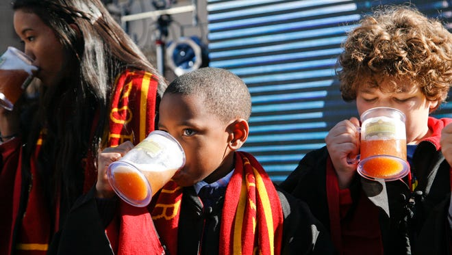 """Kids dressed as Hogwarts students drink non-alcoholic """"butterbeer"""" as Universal Parks & Resorts announces the Harry Potter attraction is coming to Universal Studios Hollywood in Universal City, Calif., Tuesday, Dec. 6, 2011."""