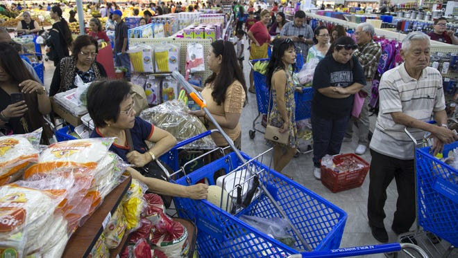 Shoppers wait to check out during the grand opening of the AZ International Marketplace in Mesa on April 20, 2016.