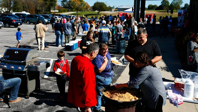 """Mikhail Kolomiza, left, and his daughter Marina Diky serve """"plov"""" to fellow church members during Bread of Life Christian Church's Russian Harvest Festival at the church grounds in Rogersville, Mo. on Oct. 22, 2016."""
