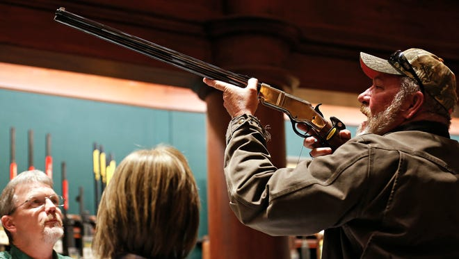 Rick Hart of Springfield examines a Henry 44-40 rifle during Black Friday shopping at the Bass Pro Shops flagship store in Springfield, Mo. on Nov. 25, 2016.