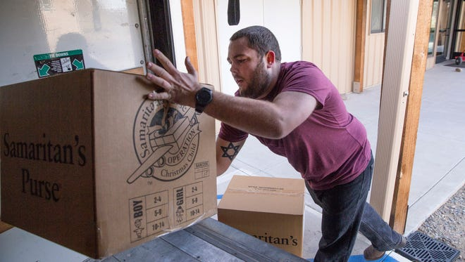 Cody Willard loads boxes in to a trailer, Monday, Nov. 20, 2017 for the Operation Christmas Child program at the Calvary Church of Farmington