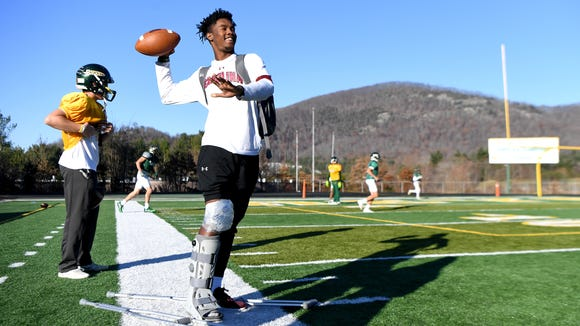 Reynolds senior Dre Dowdle helps a teammate warm up during practice at the school on Wednesday, Nov. 29, 2017. Dowdle broke his leg in a game against Roberson at the end of the regular season. He now has to encourage the Rockets, who are two games away from a state title, from the sidelines.