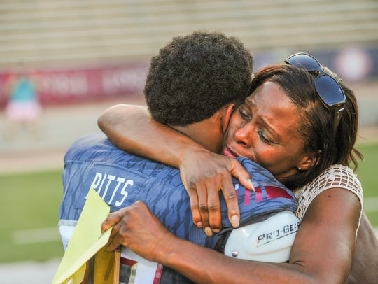 Marcia Pitts hugs her son, Troy receiver KE'Marvin,
