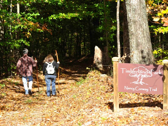 Hikers walk down the Nancy Conway Trail at the new