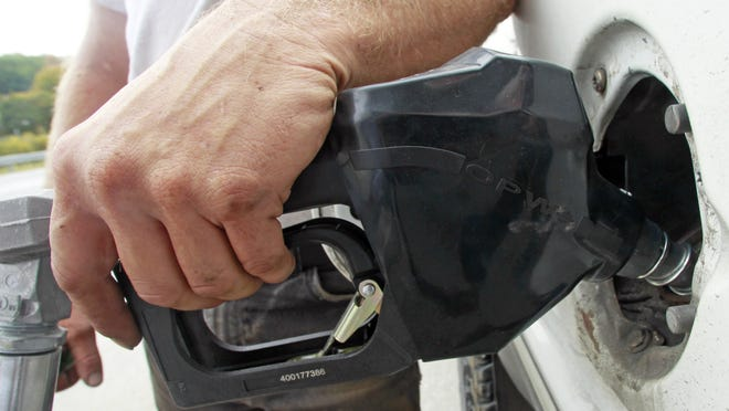 File photo of person filling vehicle with gas.