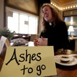Rev. Emily Goodnow, with the First Congregational United Church of Christ, waits for people who would like to ab anointed with blessed ashes for Ash Wednesday at the Ike Box on Wednesday, Feb. 10, 2016.