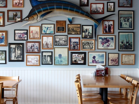 A great white marlin hangs on the wall amid photos of local fishermen.