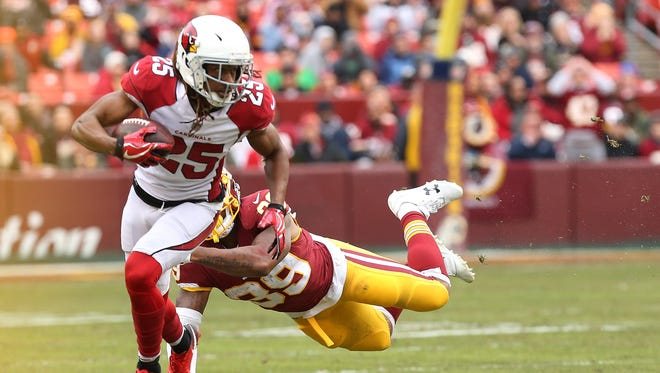 Arizona Cardinals defensive back Tramon Williams (25) returns a fumble as Washington Redskins running back Kapri Bibbs (39) attempts the tackle in the second quarter at FedEx Field.