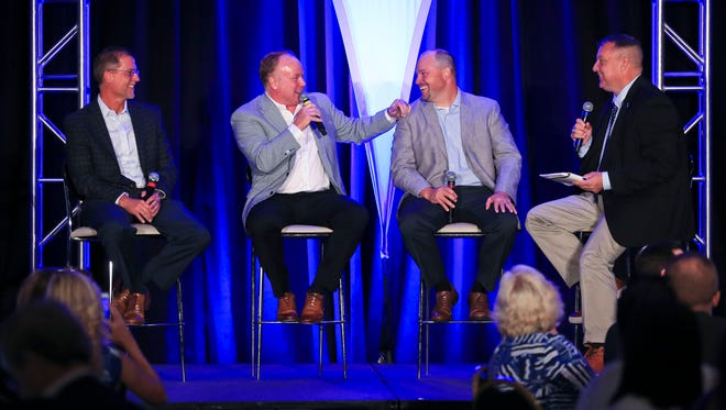 """Coach Mark Stoops, with offensive coordinator Eddie Gran, at far left,  defensive coordinator Matt House at right and former UK quarterback and host Freddie Maggard, far right at the Greater Louisville UK Alumni Association luncheon at the Galt House Friday afternoon. """"It's always fun to come (to Louisville). Particularly this year,"""" Stoops said, drawing cheers and laughs."""