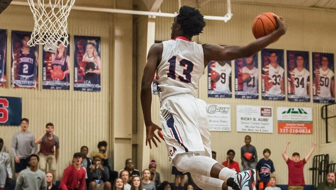 LCA's Greg Williams flies through the air for a slam dunk during the Knights' home playoff win Monday.