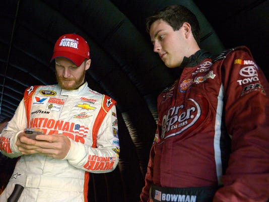 FILE - In this July 5, 2014, file photo, Alex Bowman, right, watches as Dale Earnhardt Jr. sends out a tweet, while waiting under a tunnel for driver introductions to begin, before a NASCAR Sprint Cup Series auto race at the Daytona International Speedway in Daytona Beach, Fla. Bowman will start a career-best 2nd at rain-soaked Charlotte Motor Speedway. Hurricane Matthew pushed the race from Saturday night until Sunday, but Bowman is eagerly awaiting his chance to prove himself while driving as the substitute for Earnhardt. (AP Photo/Phelan M. Ebenhack, FIle)