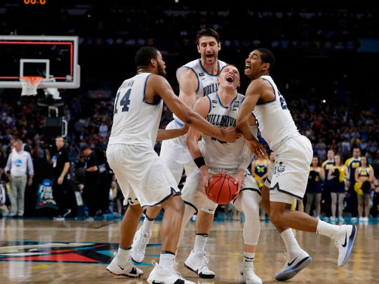 Villanova guard Donte DiVincenzo, center, celebrates with teammates at the end of the championship game against Michigan in the Final Four NCAA college basketball tournament, Monday, April 2, 2018, in San Antonio. Villanova won 79-62. (AP Photo/David J. Phillip)