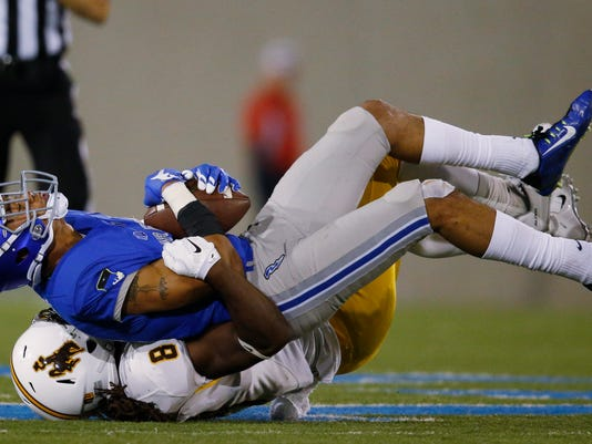 Air Force defensive back Brodie Hicks, top, is tackled after intercepting a pass by Wyoming running back Brian Hill in the second half of an NCAA college football game at Air Force Academy, Colo., Saturday, Oct. 10, 2015. (AP Photo/David Zalubowski)