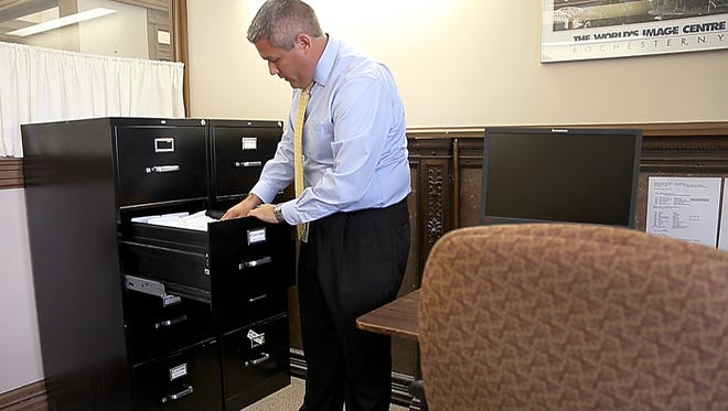 Adam Bello, Monroe County clerk, with 20,000 unprocessed opt-out forms for pistol permit holders sitting in a filing cabinet in the Monroe County office building.