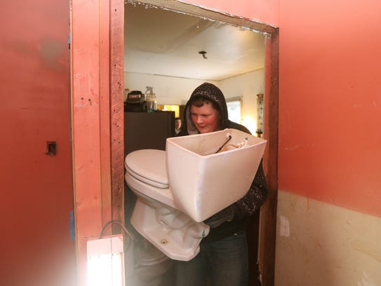 Ethan Truax, 14, carries a new toilet into a home as part of the Flower City Work Camp. Local teens volunteer part of their spring break to help families spruce up their houses.