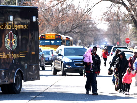 Adults and students walk away from John R. King Academy