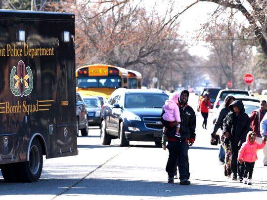 Adults and students walk away from John R. King Academy and past a DPD Bomb Squad truck after the scene is declared safe by first responders.