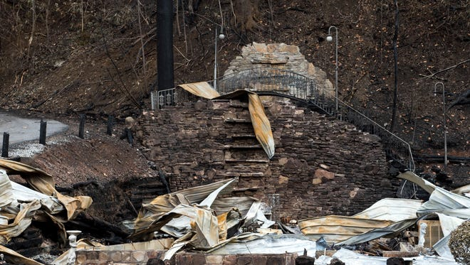 """This Wednesday, Dec. 7, 2016, photo, shows the remains of Cupid's Chapel of Love, in Gatlinburg, Tenn. Amid deadly wildfires in the Great Smoky Mountains, the city nicknamed """"the wedding capital of the south"""" lost one of its most recognizable places to get hitched. The chapel, a white wood log building with a green tin roof and waterfall around back, hosted about 20,000 weddings over more than two decades. It's uncertain whether the chapel will ever be rebuilt.  (Andrew Nelles/The Tennessean via AP)"""