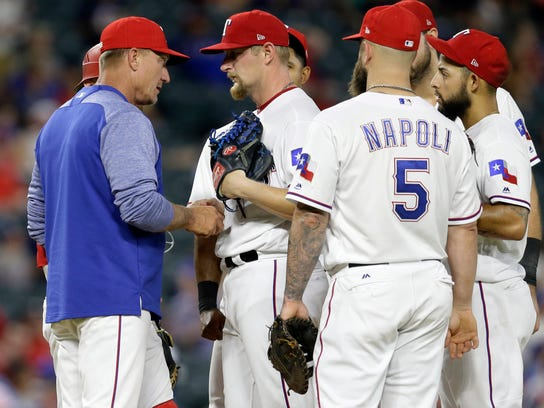 Texas Rangers manager Jeff Banister, left, talks with starting pitcher Austin Bibens-Dirkx, second from left, as Mike Napoli (5) and Rougned Odor, right, listen before Bibens-Dirkx was replaced by Jeremy Jeffress during the fifth inning of a baseball game against the Tampa Bay Rays on Wednesday, May 31, 2017, in Arlington, Texas. (AP Photo/Tony Gutierrez)