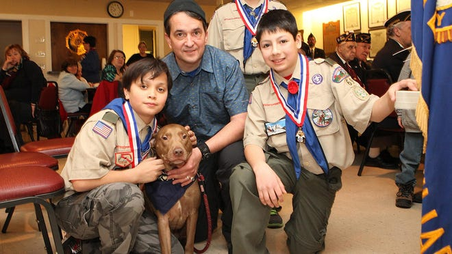 Michael Petronino, 11, holding his dog Adobo, Chris Petronino, Vincent Lepore, 12, and Frannkie Lepore, 13, all from Boonton Twp. The boys and the dog were honored by the American Legion Auxiliary at Denville Post 390 for helping save Chris Petronino from a bear attack that accurred earlier this fall. Wednesday, February 17, 2016. Denville, NJ.