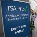 Travelers walk past a TSA PreCheck application center at New York LaGuardia Airport. Other application centers are in more surprising locations.