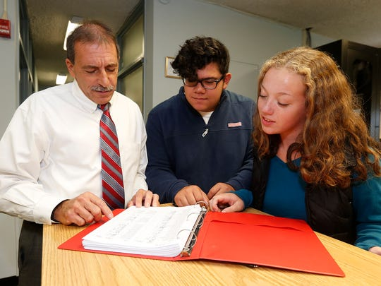 High school principal Vincent Carella, left, with students