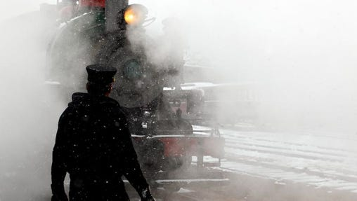 Steam and snow surround Mike Grimm waits for the engine of a vintage 1880 train to back into position in Hill City, S.D., Thursday morning, Sept. 11, 2014. Riders on the popular summertime tourist attraction got a very wintertime view as a storm brought as much as 8 inches of snow to parts of the Black Hills. Snowfall in downtown Rapid City marked the earliest such event since 1888; that was before South Dakota was even a state.