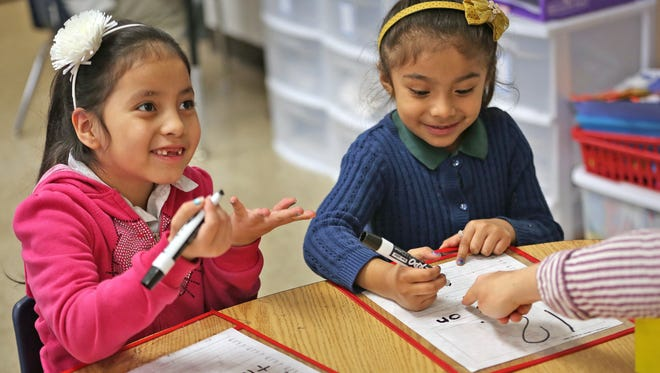 Kindergartners Ivania (left) and Jackie worked on reading and writing with their teacher, Liz Amadio, at Enlace Academy on April 14, 2015. During the past school year, 55 percent of students at the charter school were English language learners.
