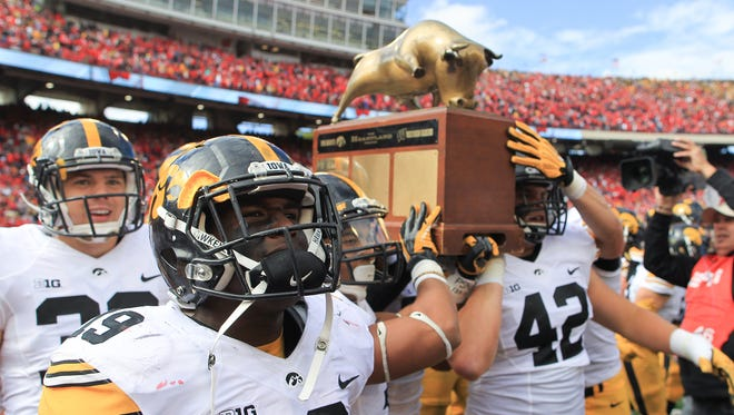 Iowa teammates bring theHeartland Trophy to a Hawkeye fan section following their 10-6 win over Wisconsin at Camp Randall in Madison on Saturday.