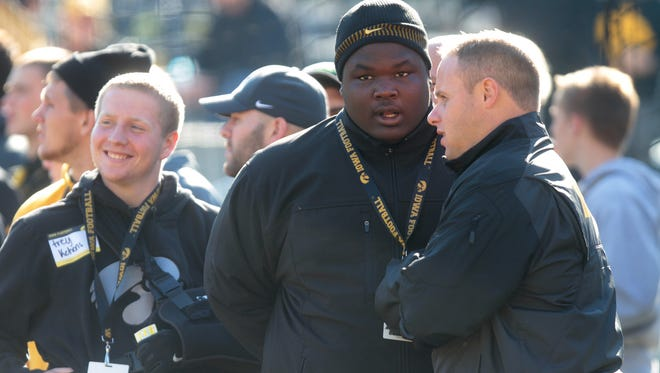 Iowa recruiting coordinator Seth Wallace, right, talks with North Fayette Valley's Juan Harris, an Iowa commit, prior to the Hawkeyes' game against Indiana at Kinnick Stadium last year.