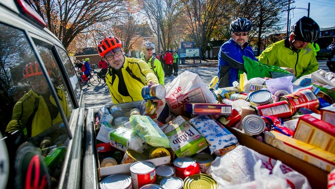 Joachim Kragl, Greg Stump and Victor Bosley unload collected food items into the bed of a pickup truck Saturday. The items were to be donated to the York County Food Bank. Cyclists participating in Cranksgiving rode to area stores on bikes collecting food items from a list.