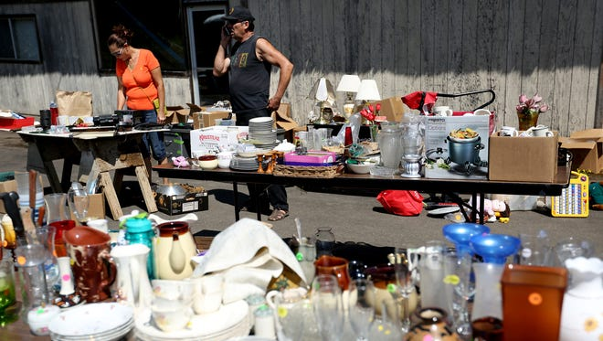 Isabel Ramos, 54, of Baldwin Park, Calif., and her friend Ricardo Nolazco, 56, of Mill City, look through items for sale at a garage sale during the Dog Daze event in Mill City, Ore., on Saturday, Aug. 15, 2015.