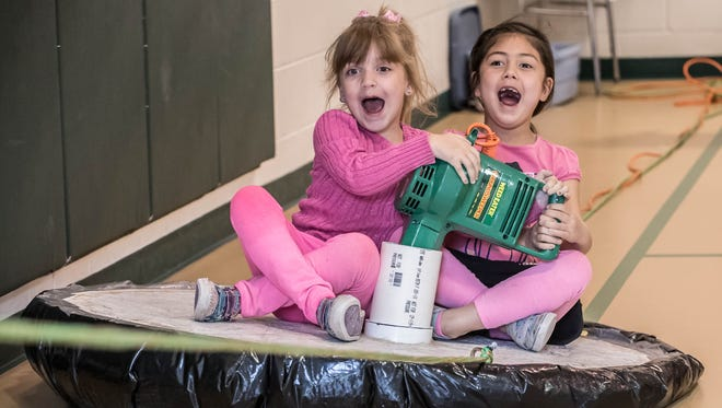 Purdy Elementary Kindergarten students Sophia Rice, left, and Alia Diamante ride a hovercraft powered by a leaf blower during their science day.
