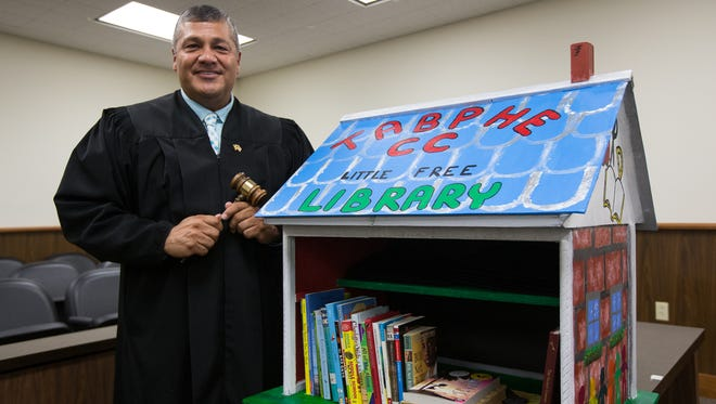 Justice of the Peace, Precinct One, Place One, Judge Joe Benavides, stands next to the Little Free Library that will be installed in his courtroom, Tuesday, Nov. 1, 2016