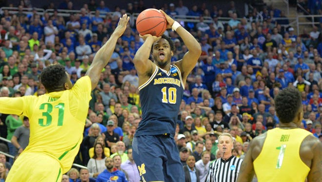 Michigan Wolverines guard Derrick Walton Jr. shoots over Oregon Ducks guard Dylan Ennis in the final seconds of U-M's 69-68 loss in the 2017 NCAA tournament Midwest Regional at Sprint Center on Thursday, March 23 in Kansas City.