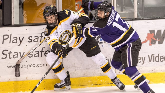 Canton's Matt Roy (left) takes a hit to move the puck for Michigan Tech during the 2016-17 season.