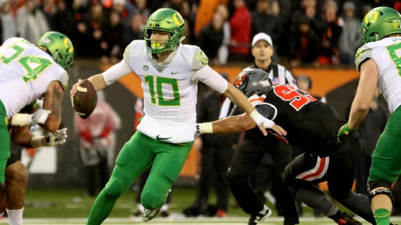 Oregon's Justin Herbert (10) rushes in the second half of the Oregon vs. Oregon State Civil War football game at Oregon State University in Corvallis on Saturday, Nov. 26, 2016. The Beavers won the game 34-24.