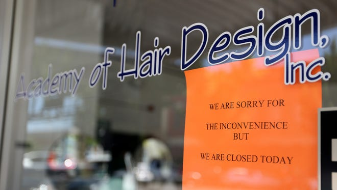 A sign on the door says Academy of Hair Design in downtown Salem has closed. Photographed on Thursday, July 13, 2017.